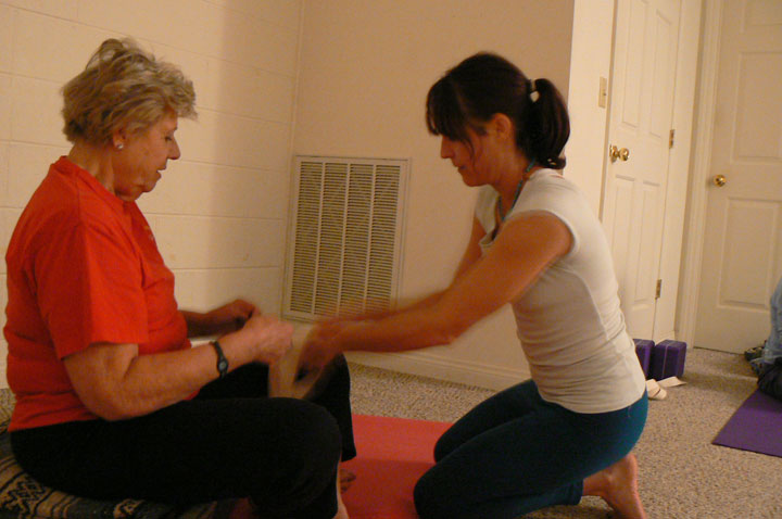Nicole assists a student with an injured knee to aid in the execution of  yoga poses.